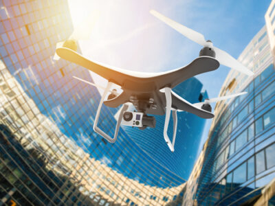 Drone with digital camera flying in a modern city at sunset: 3D rendering